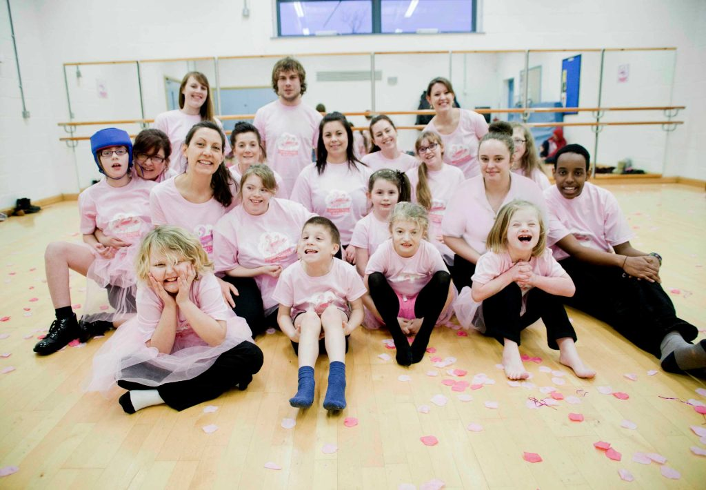 Flamingo Chicks and volunteers pose in front of ballet studio mirrors