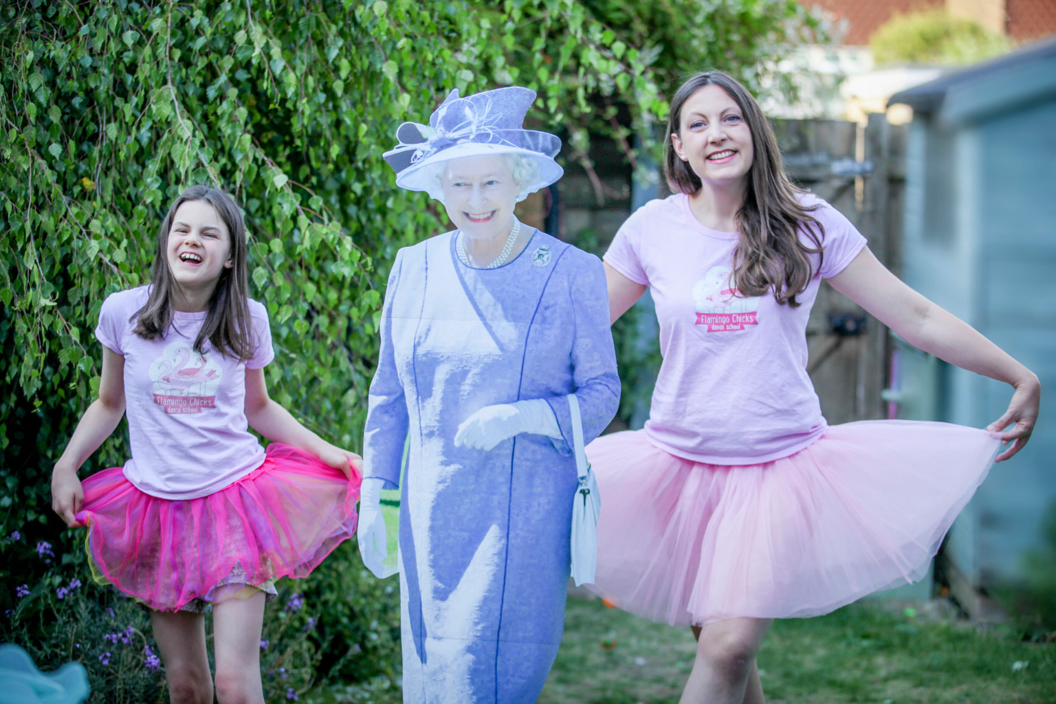 Flamingo Chicks CEO Katie and her family curtsey with a cut out of the Queen celebrating our Queen's Award win