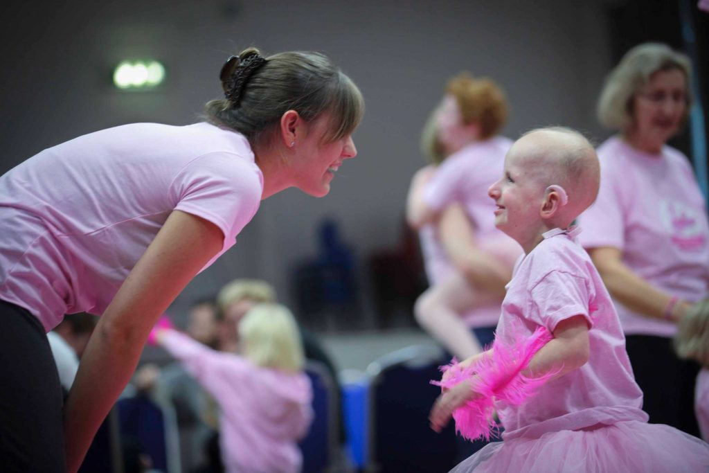 A dance teacher shares a smile with one of our Flamingo Chicks children