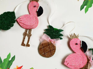 Garland of pink glittery flamingos and golden glittery pineapples on a white string
