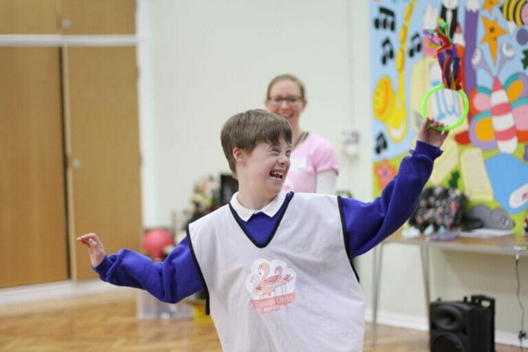 A boy in a Flamingo Chicks' tabard smiles to the right and poses with his arms aloft as he enjoys one of our classes