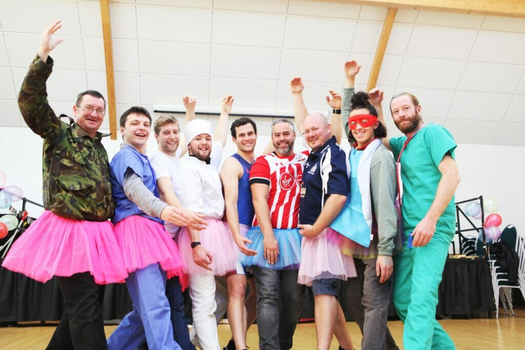 Group of dads pose in tutus and superhero outfits