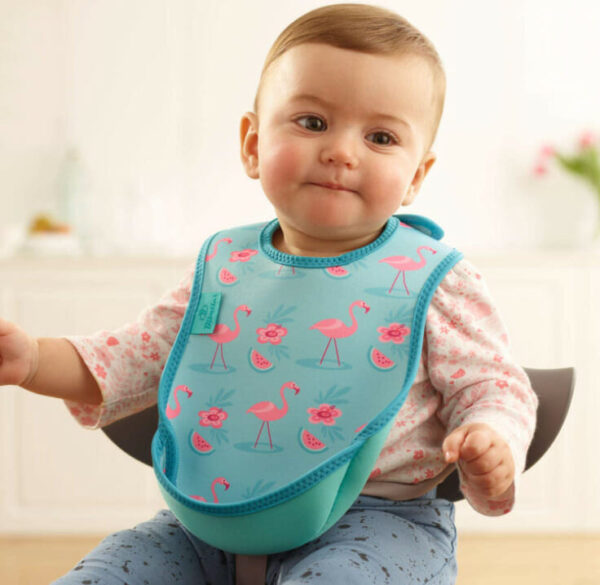 Baby sitting in a kitchen wearning a turquoise bib with pink flamingos on