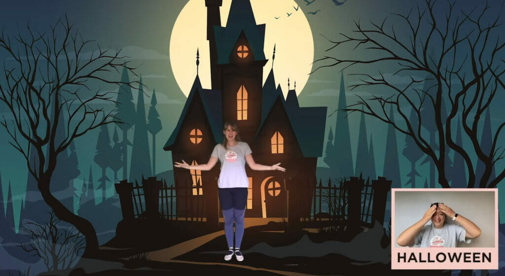 Halloween Spooktacular virtual class: Rhiannon stands in front of a haunted house at night with a full moon behind