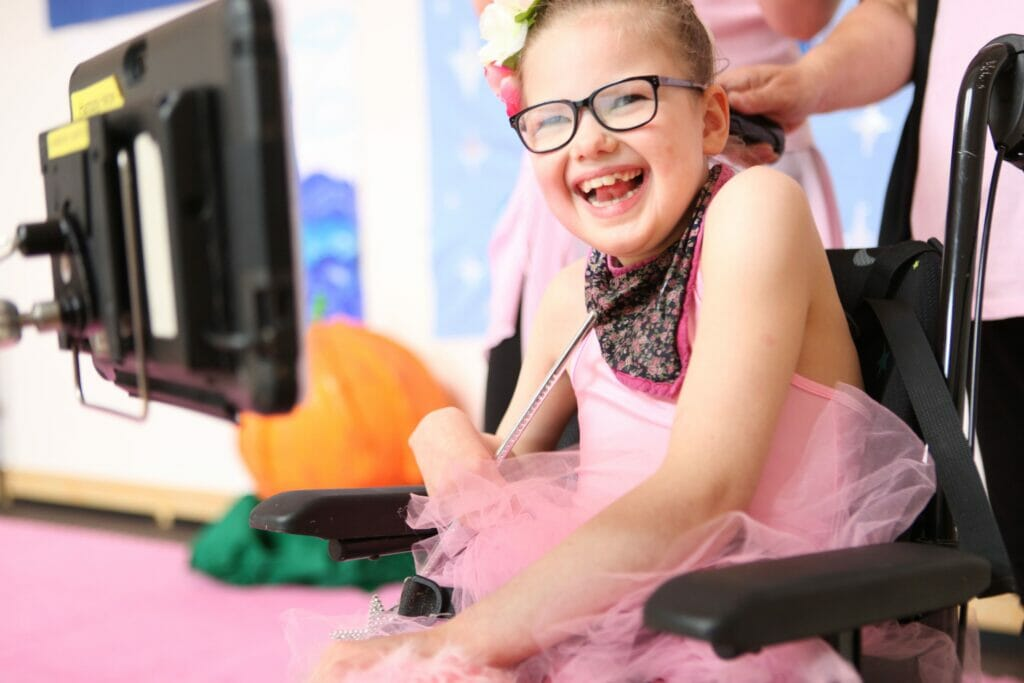 One of our flamingo chicks dancers smiles from her wheelchair