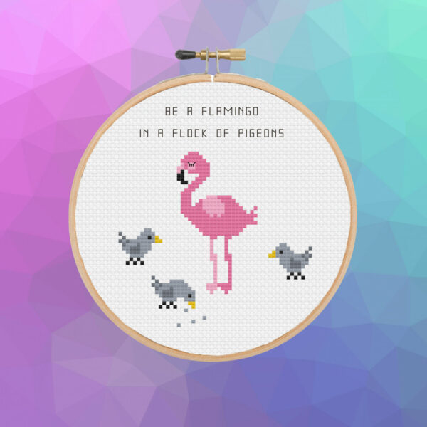 circular wooden cross stitch frame with flamingo and three pigeons stitched on, text reads 'be a flamingo in a flock of pigeons'