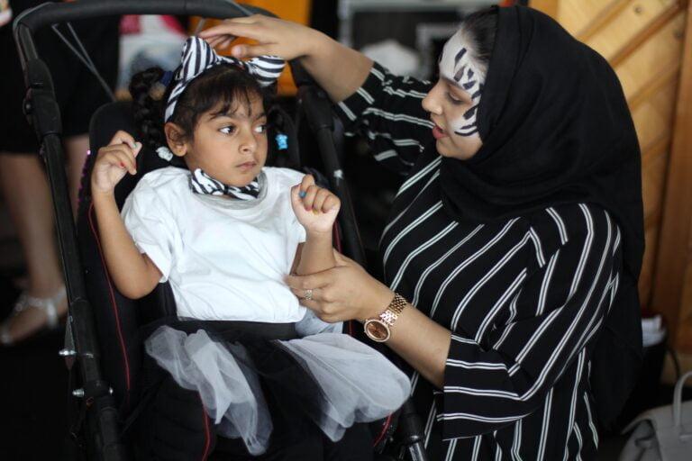 A dance helper with zebra face paint puts zebra ears on a child