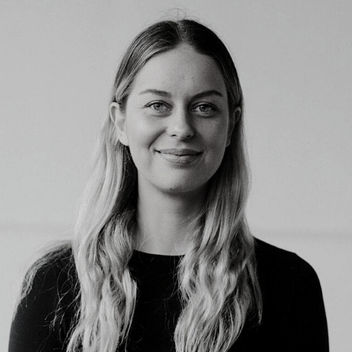 Black and White photo of dance teacher Olivia Riley. She is smiling, has long blonde hair, and is wearing a dark jumper.