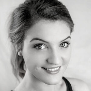 Black and white photo of dance teacher - Sophie Cottle. She is smiling and looking up towards the camera.
