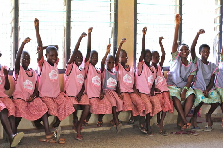 A group of pupils in Ghana raise their arms to create a Flamingo neck