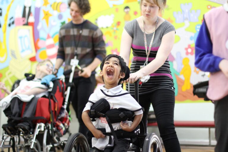 A young boy in a wheelchair gives a huge smile as he takes part in a Flamingo Chicks class, supported by his learning assistant