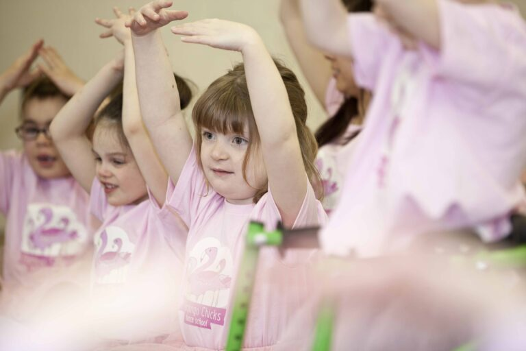 A girl in a pink t-shirt and tutu poses with her arms in fifth position
