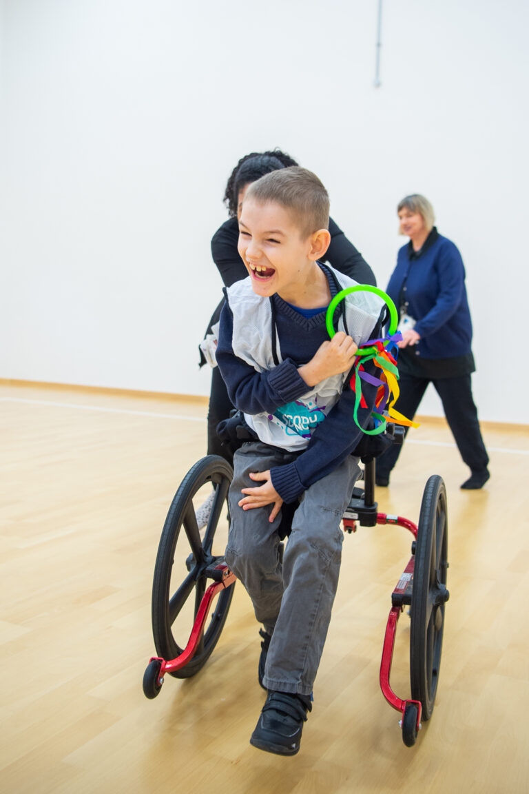 A boy in a wheelchair smiles and plays with a ribbon ring