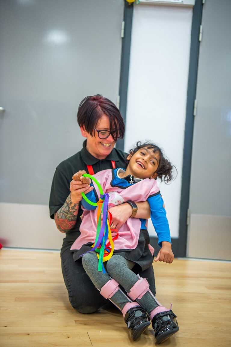 A girl and her carer play with multi-coloured ribbons in a Flamingo Chicks class