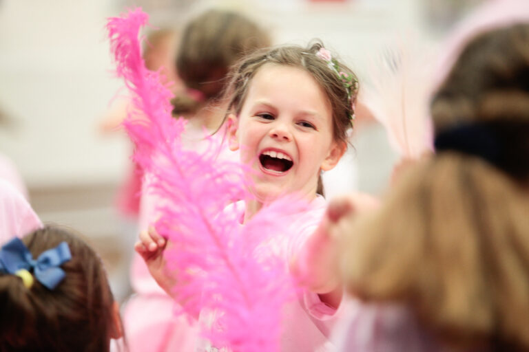 A girl plays with a huge pink feather in a Flamingo Chicks class