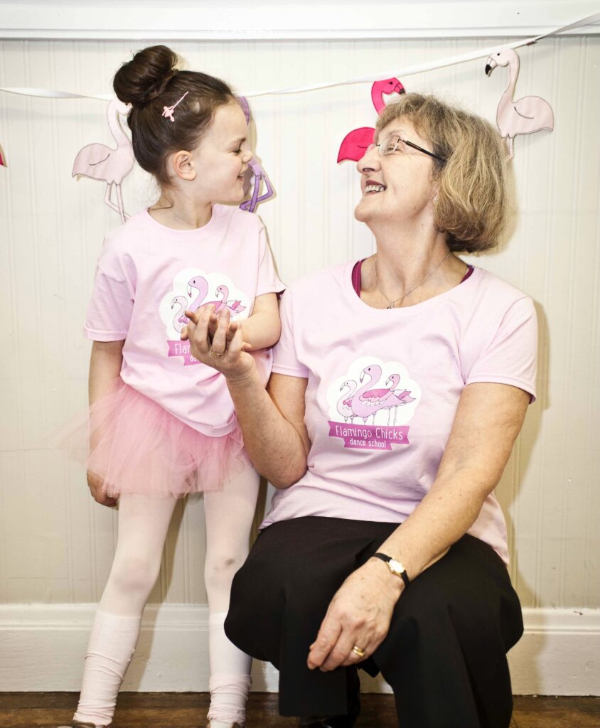 An older woman crouches next to a young girl in a ballet tutu and Flamingo Chicks t-shirt